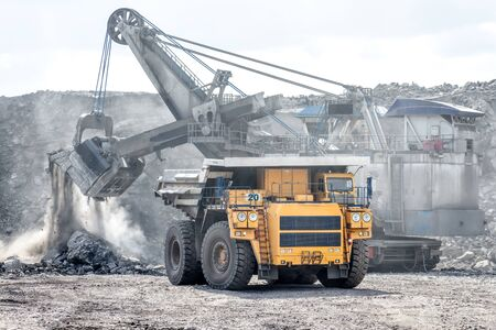 Ore loading with a powerful excavator. Loading a large mining truck. Stok Fotoğraf