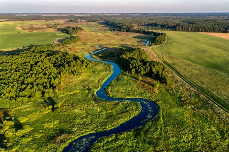 A small river flowing through meadows and agricultural fields. Aerial view. Evening shot with the setting sun. Standard-Bild