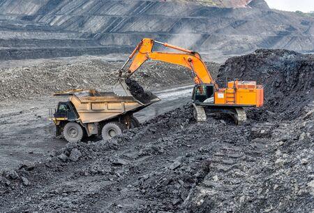 La minería del carbón en una cantera. Una excavadora hidráulica carga un camión volquete. Foto de archivo