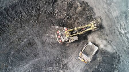 Cable excavator loads overburden from the body of a mining truck. Stok Fotoğraf