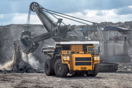 Open mountain quarry. Loading coal into a mining truck.