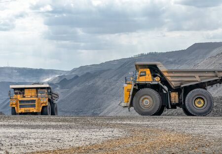 Rock transportation by dump trucks. Large quarry yellow truck. Transport industry. Mining truck is driving along a mountain road.
