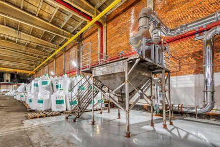 Grand entrepôt industriel de produits chimiques. De grands sacs blancs remplis de poudre sont disposés en longues rangées.
