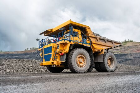 Grand camion à benne basculante de carrière. Industrie des transports. Un camion minier roule le long d'une route de montagne. Camion de carrière transporte du charbon extrait. Banque d'images