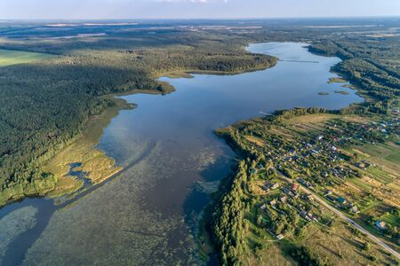 Beautiful aerial shot of a large forest lake. Summer landscape with the setting sun. Typical view for the Central European plain. Banco de Imagens