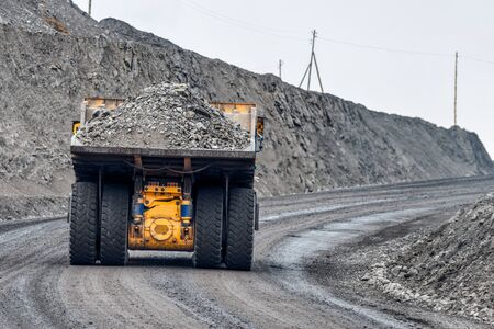 Quarry truck carries coal mined. A mining truck is driving along a mountain road. Road for the movement of heavy trucks. 版權商用圖片 - 132331978