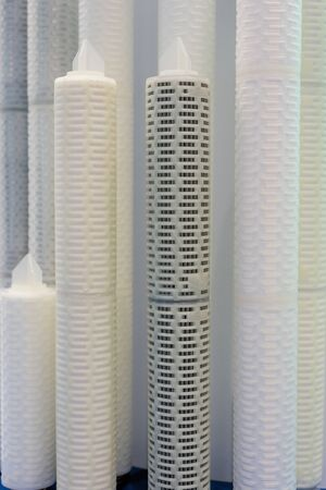 Large and long industrial filters. White high plastic cylinders with perforated wall.