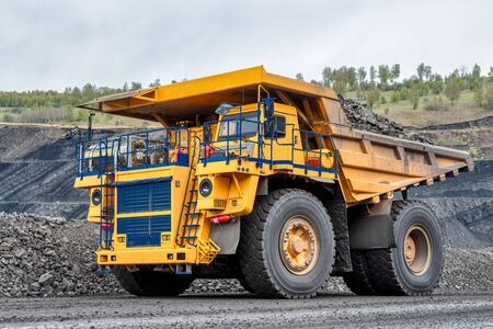 Quarry truck carries coal mined. A mining truck is driving along a mountain road. Road for the movement of heavy trucks.