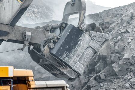 Powerful and large excavator bucket. Loading of minerals into the body of a mining truck.