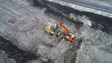 Coal mining in a quarry. A hydraulic excavator loads a dump truck. The process of loading mining trucks with a excavator.
