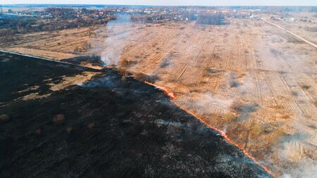 Forest and field fire. Dry grass burns, natural disaster. Aerial view. Fire spreads as a united front and approaches the village. Stockfoto