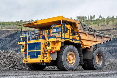 Il camion della cava trasporta il carbone estratto. Un camion da miniera sta guidando lungo una strada di montagna. Strada per la circolazione dei mezzi pesanti.