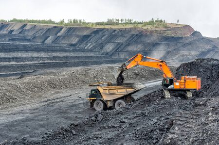 Coal mining in a quarry. A hydraulic excavator loads a dump truck. Banco de Imagens