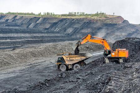 Wydobycie węgla w kamieniołomie. Koparka hydrauliczna ładuje wywrotkę.