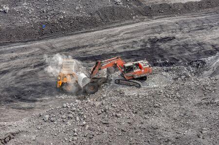 Coal mining in a quarry. A hydraulic excavator loads a dump truck. Stock Photo