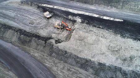 Coal mining in a quarry. A hydraulic excavator loads a dump truck. Imagens