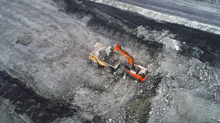 Coal mining in a quarry. A hydraulic excavator loads a dump truck.