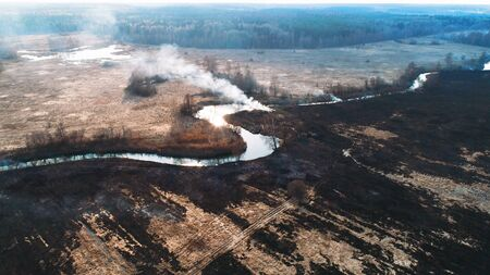 Forest and field fire. Dry grass burns, natural disaster. Aerial view. Smooth flight over the place of fire, a small stream blocks the path to the fire. Stock Photo