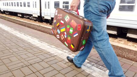A man is walking along a railway platform. Holding an old suitcase in his hands.