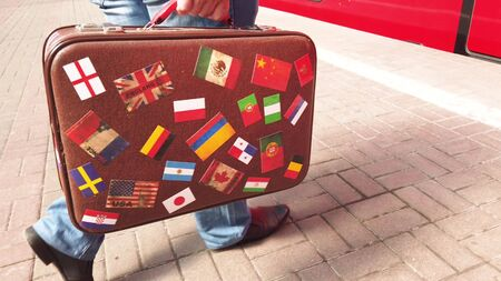 A man with a vintage suitcase comes into the vestibule of the train. The suitcase is decorated with stickers with the image of flags of different countries. Stock Photo