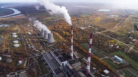 Power plant generating heat and electricity. High pipes and cooling towers are visible. Aerial view.