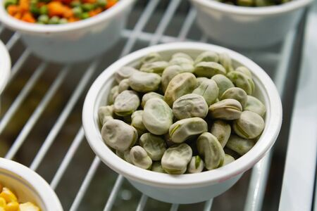 Frozen beans lies in a white cup. Next to the plates are other frozen vegetables and fruits.