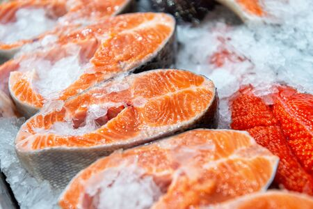 Chilled steaks of red fish. Pieces of fish lie on ice.