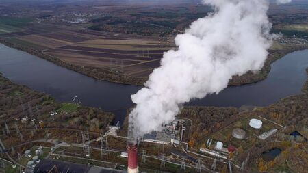 State District Power Station aerial view. High factory chimney, a powerful stream of steam comes from the chimney. Autumn landscape. Smooth lowering the camera from top to bottom. 스톡 콘텐츠