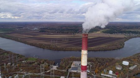 State District Power Station aerial view. High factory chimney, a powerful stream of steam comes from the chimney. Autumn landscape. Smooth lowering the camera from top to bottom. Stock Photo