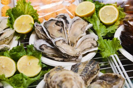 Open frozen oysters are in the freezer. Shellfish lie on a plastic plate surrounded by slices of lemon and lettuce. Seafood at the storefront.