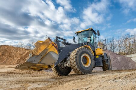 A wheel loader travels through a sand and gravel warehouse.