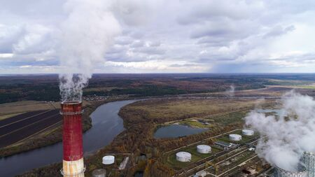 State District Power Station aerial view. High factory chimney, a powerful stream of steam comes from the chimney. Autumn landscape. Flying near a chimney..