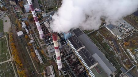 State District Power Station aerial view. High factory pipe, a powerful stream of steam comes from the pipe.. Autumn landscape