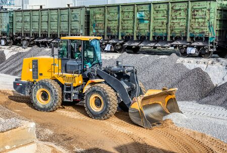 A wheel loader picks up gravel into a bucket. Transportation of inert materials for concrete production.
