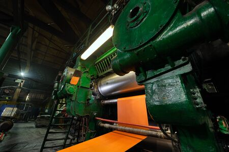 Factory for the production of conveyor belts. Wide orange polyamide canvas in a conveyor belt making machine. Stock Photo