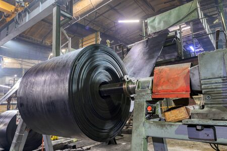 Interior of a factory for manufacturing rubber conveyor belts. Large rolls of black rubber tape.
