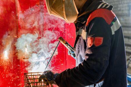 A welder is welding a steel billet for a pile.