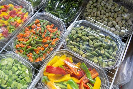 Frozen vegetables, fruits and berries. Food products are poured into rectangular plastic trays. Shop window.
