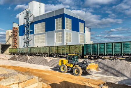 Wheel loader works in a warehouse of sand and gravel. Flyover for unloading railway freight cars.