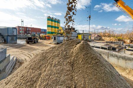 A conveyor belt spills a large pile of sand.
