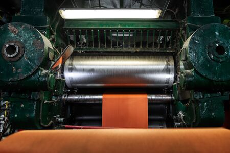 Factory for the production of conveyor belts. Wide orange polyamide canvas in a conveyor belt making machine.