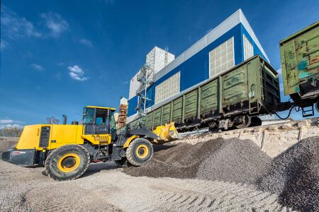 Wheel loader picks gravel in the bucket. Work on a flyover for unloading railway freight cars.