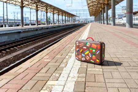 A retro suitcase stands on an empty train platform. Standard-Bild
