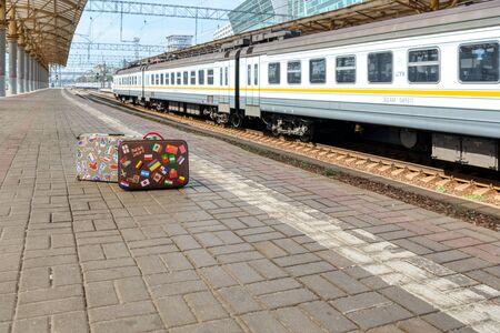 Little retro traveler suitcase on a passenger platform. Empty train station.