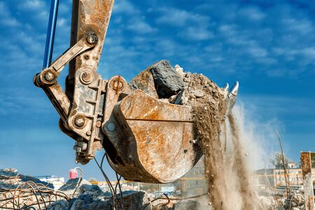 An excavator spills soil out of a rusty old bucket.