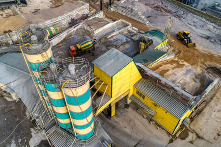 Cement storage silos are painted in yellow-green stripes.