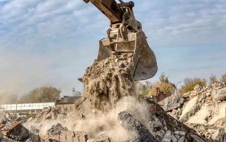 An excavator spills soil out of a bucket.