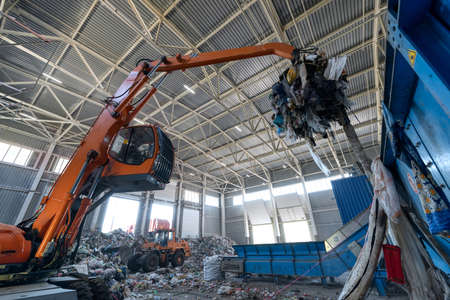Waste sorting and recycling plant. Loader and grab crane are handling waste Foto de archivo