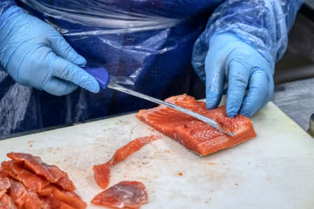 The process of manual filleting of red fish. The worker cuts the fish into pieces with a knife.