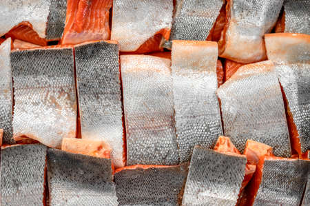 Many pieces of salmon and trout fillet, close-up photo.